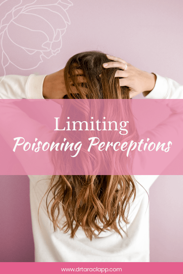 pink background - woman facing away with hands to head - Limiting Poisonous Perceptions - Article by Dr. Tara Clapp, ND