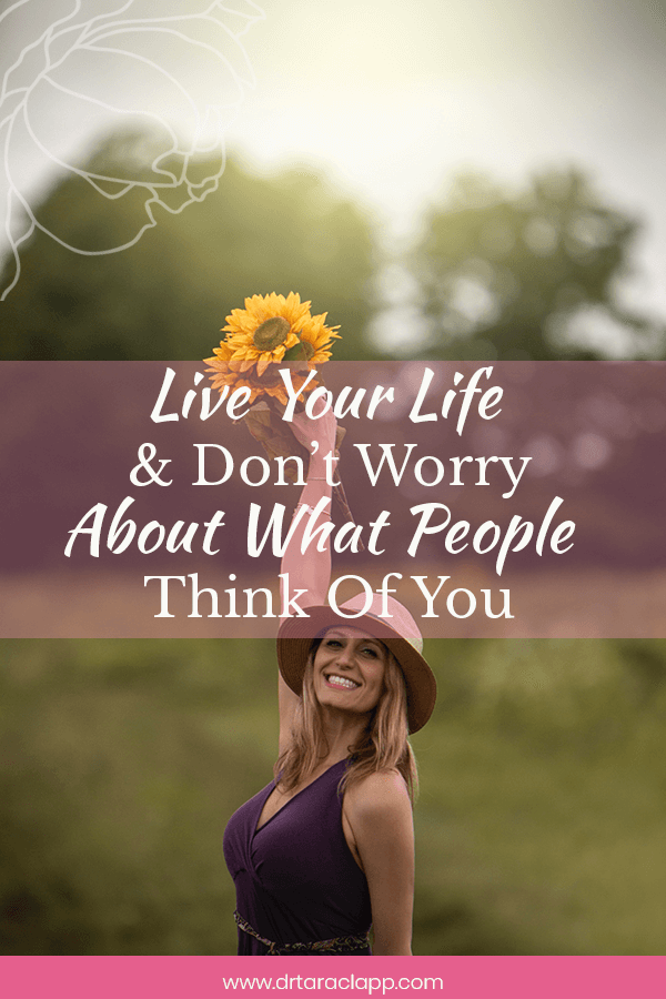 woman holding flowers over her head - Live Your Life & Don't Worry About What People Think of You - Article by Dr. Tara Clapp, ND