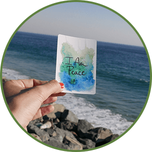 Woman's hand holding an affirmation card - I am peace